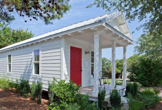 ตัวบ้านแนวยาวสี่เหลี่ยมผืนผ้า หลังคาแบบหน้าจั่ว ใช้ประตูไม้สีแดง