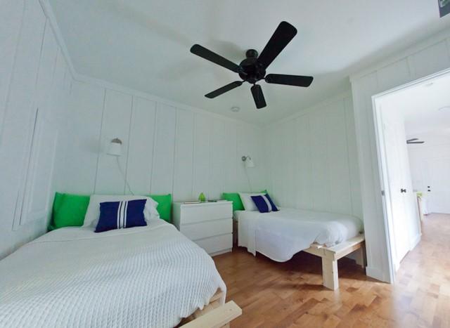 ห้องนอนสีขาวเตียงแยก พัดลมเพดานสีดำ