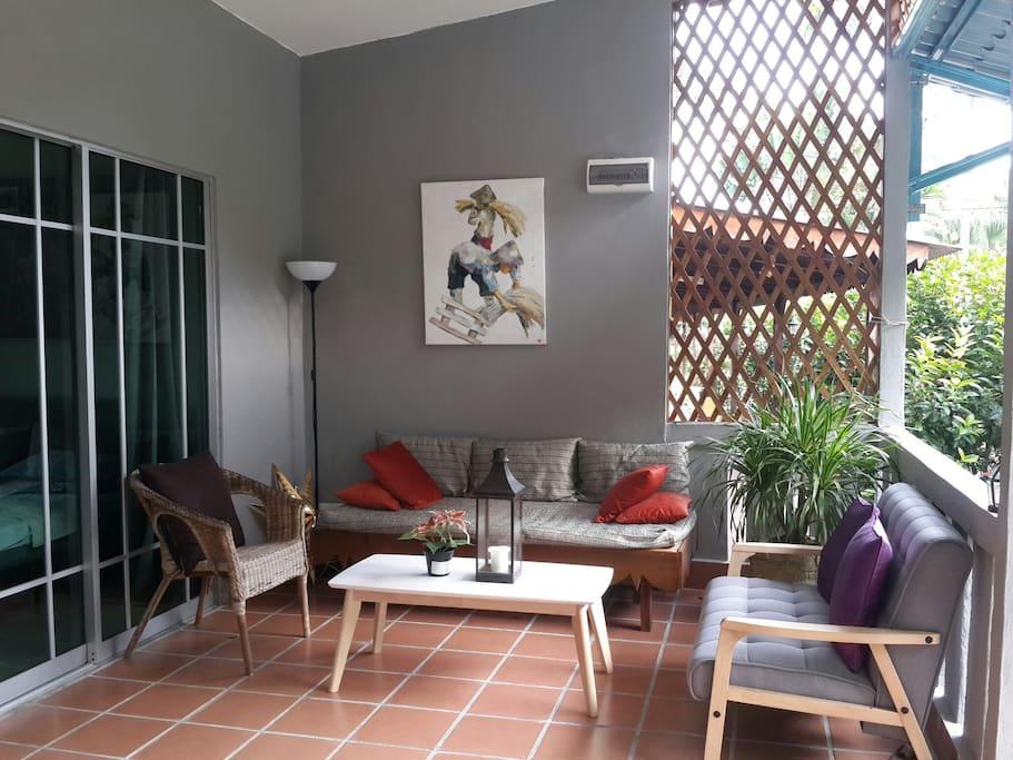 ระเบียงบ้านขนาดกว้างพอเหมาะจัดวางด้วยโต๊ะรับประทานอาหารชุดเล็ก พื้นระเบียงปูด้วยกระเบื้องสีแดงอิฐ ตัดกับสีผนังซึ่งเป็นสีเทาเข้ม