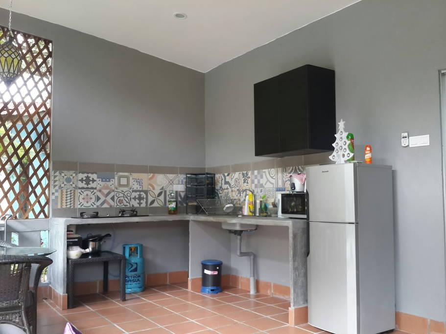 ห้องครัวทำเคาเตอร์ถาวรด้วยปูนเปลือย ปูพื้นด้วยแผ่นกระเบื้องสีแดง ผนังสีเทาเข้ม ตัดกันสวยมาก
