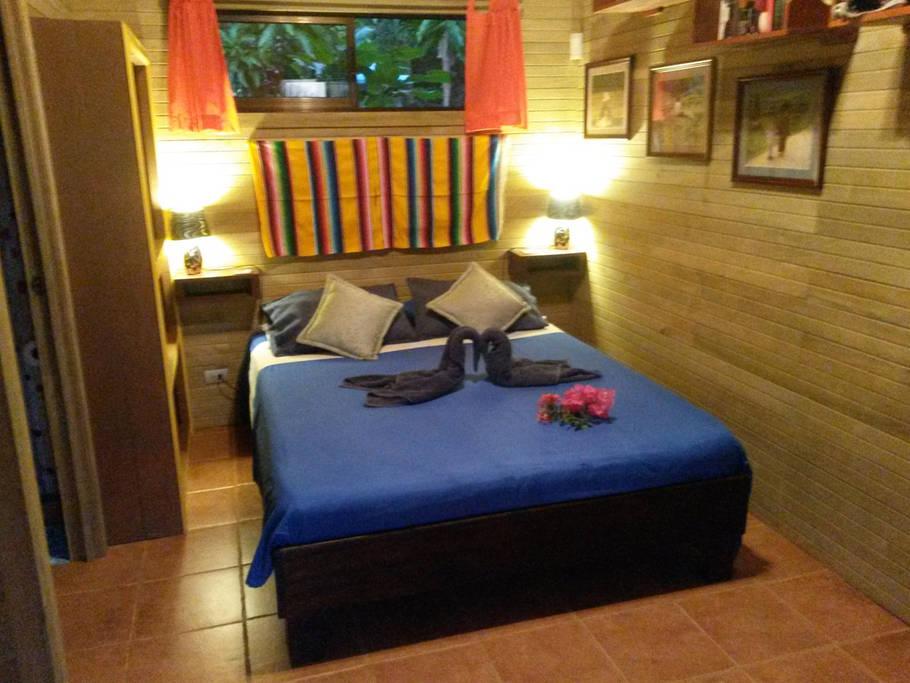 ห้องนอนตกแต่งเรียบง่าย มีโครมไฟหัวเตียง 2 ตัว มีช่องรับลมจากภายนอกด้วยหน้าต่างบานเล็ก