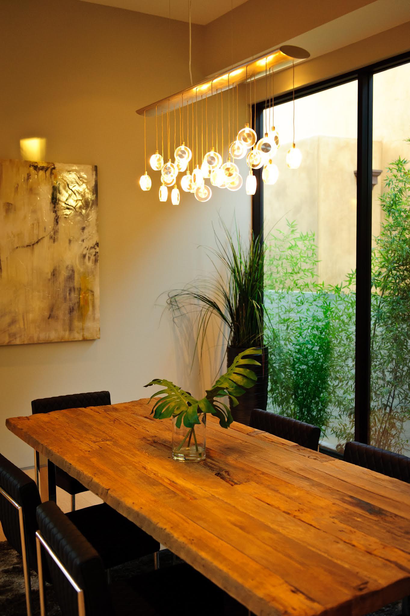 ตกแต่งด้วยโต๊ไม้จริงตัวใหญ่ ใช้กระจกเป็นผนังเพื่อให้มองเห็นสวนเขียวๆ เพิ่มความสดชื่นแก่ผู้อยู่อาศัย