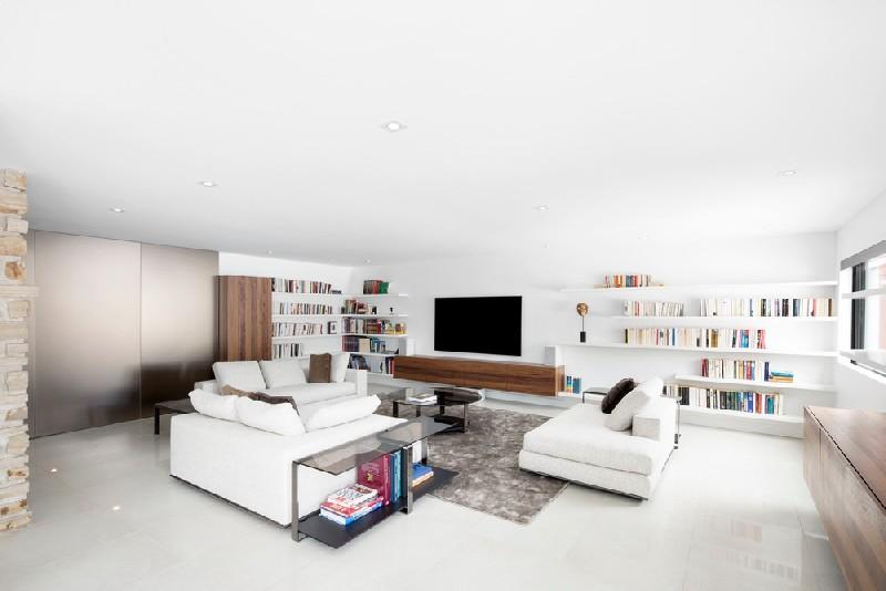 ห้องรับแขกสีขาวกับชั้นวางหนังสือ