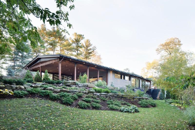 บ้านสร้างบนเชิงเนินเล็กน้อย รอบๆบ้านตกแต่งสวนและหญ้าเขียวขจี