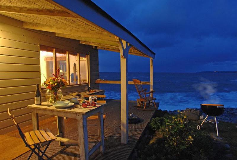 ระเบียงหน้าบ้านขนาดเล็กพอเหมาะ มีชุดโต๊ะไม้เก่าเล็กๆ สำหรับนั่งจิบกาแฟ