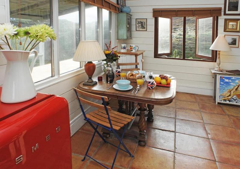 ภายในมีมุมโต๊ะอาหารด้านซ้ายของตัวบ้าน ผนังบ้านสีขาวตัดกับพื้นกระเบื้องสีแดงอิฐ