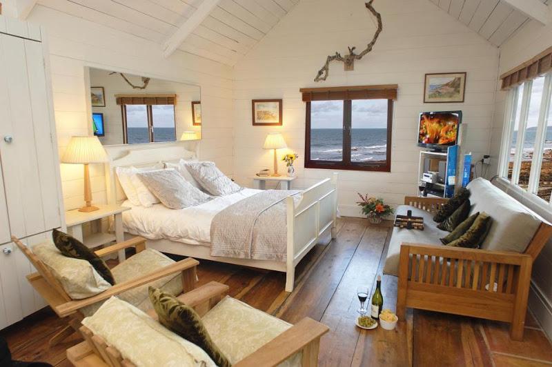 มุมห้องนอนจัดไว้ด้านขวาของบ้าน มีโซฟาไม้ตัวเล็กวางบริเวณใกล้เตียง