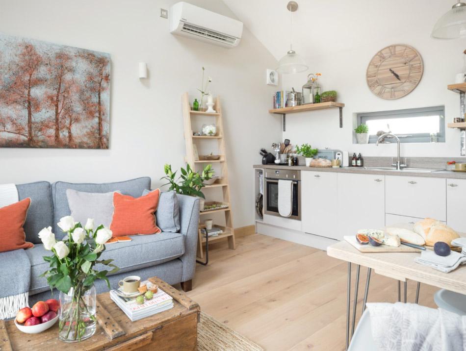 ในห้องครัวตกแต่งด้วยโซฟาตัวเล็กๆโทนฟ้าเทา กับหมอนสีส้มใบเล็ก